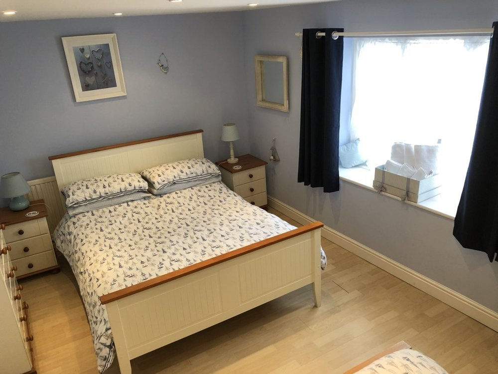 Bedroom 1 - Double bed, single bed, wardrobe, chest of drawers, chair, lamps, dimmer lights  Access to Bathroom with bath, sink and WC.