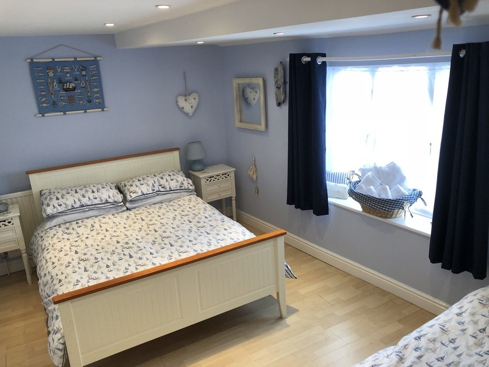 Bedroom 2 -double bed, single bed, wardrobe, chest of drawers, lamps, dimmer lights, cot, emergency exit to street level  Access to Bathroom with shower, sink and WC.