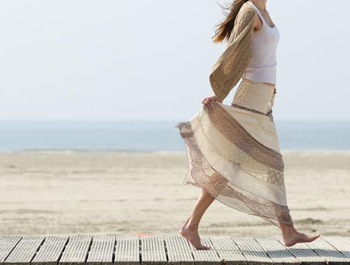 woman-walks-barefoot-beach-dress
