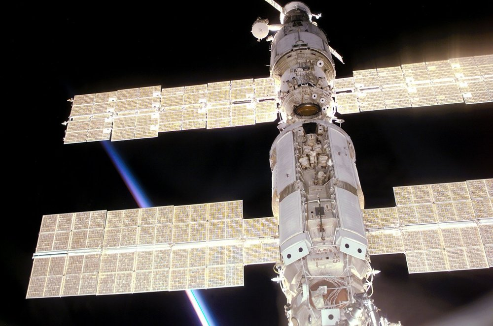 """This view of the International Space Station (ISS) was taken while it was docked with the Space Shuttle Atlantis and shows parts of all but one of the current components. From the top are the Progress supply vehicle, the Zvezda service module, and the Zarya functional cargo block (FGB). The Unity, now linked to the docking system of the Atlantis in the cargo bay, is out of view at bottom. A multicolored layer signals a sunset, in accordance with the stations normal direction of travel and normal orientation, this is also confirmed by the surrounding sequence of images."""
