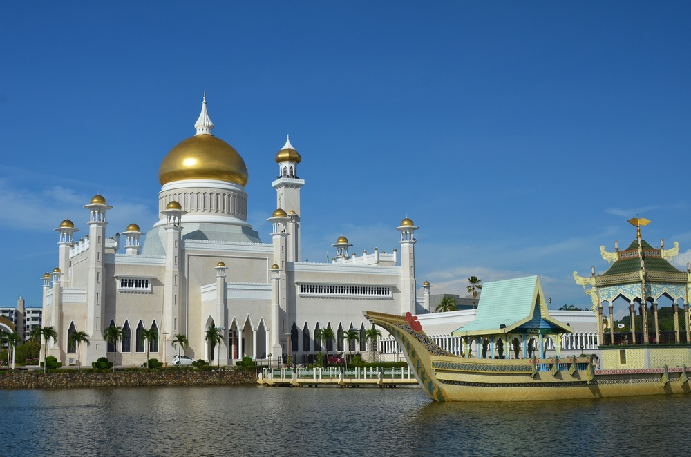 "The Omar Ali Saifuddien Mosque in Brunei's capital is named after the 28th Sultan, the father of the reigning Sultan Hassanal Bolkiah. The mosque's 52 m (171 ft) high main dome is completely covered in pure gold. The structure is known as one of the most beautiful mosques in Asia Pacific. Completed in 1958, the mosque combines Mughal and Italian architecture. The barge in the lagoon surrounding the mosque was installed to commemorate the 1,400th anniversary of the ""coming down of the Quran"".  As a place of worship for the Muslim community in Brunei, the mosque dominates the skyline of the capital city."