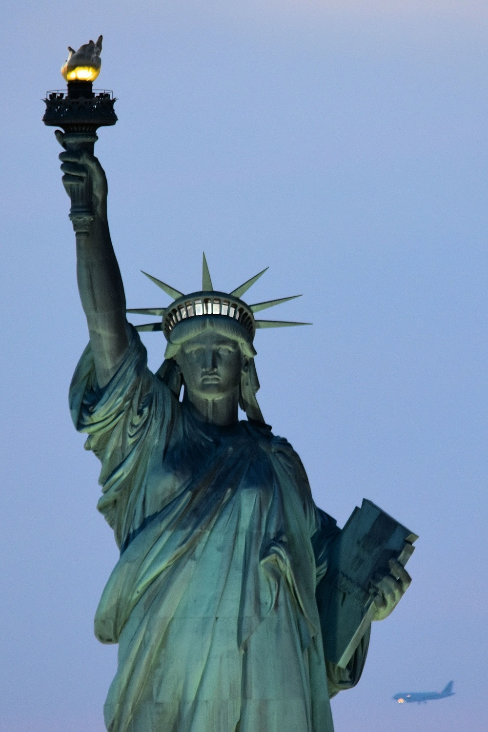 Positioned at the entrance to the harbors of New York and Jersey City at the mouth of the Hudson River, the 93 m (305 ft) tall Statue of Liberty is seen as a welcoming symbol of freedom and democracy for countless immigrants from all over the world.