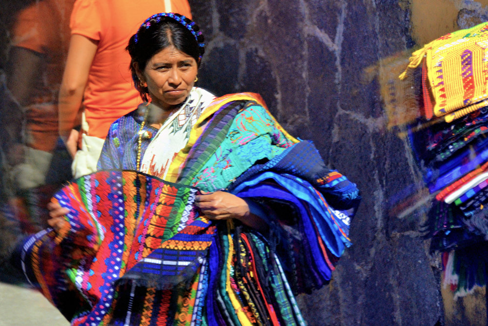 A Mayan woman selling traditional fabrics to tourists at Lake Atitlan, Guatemala.