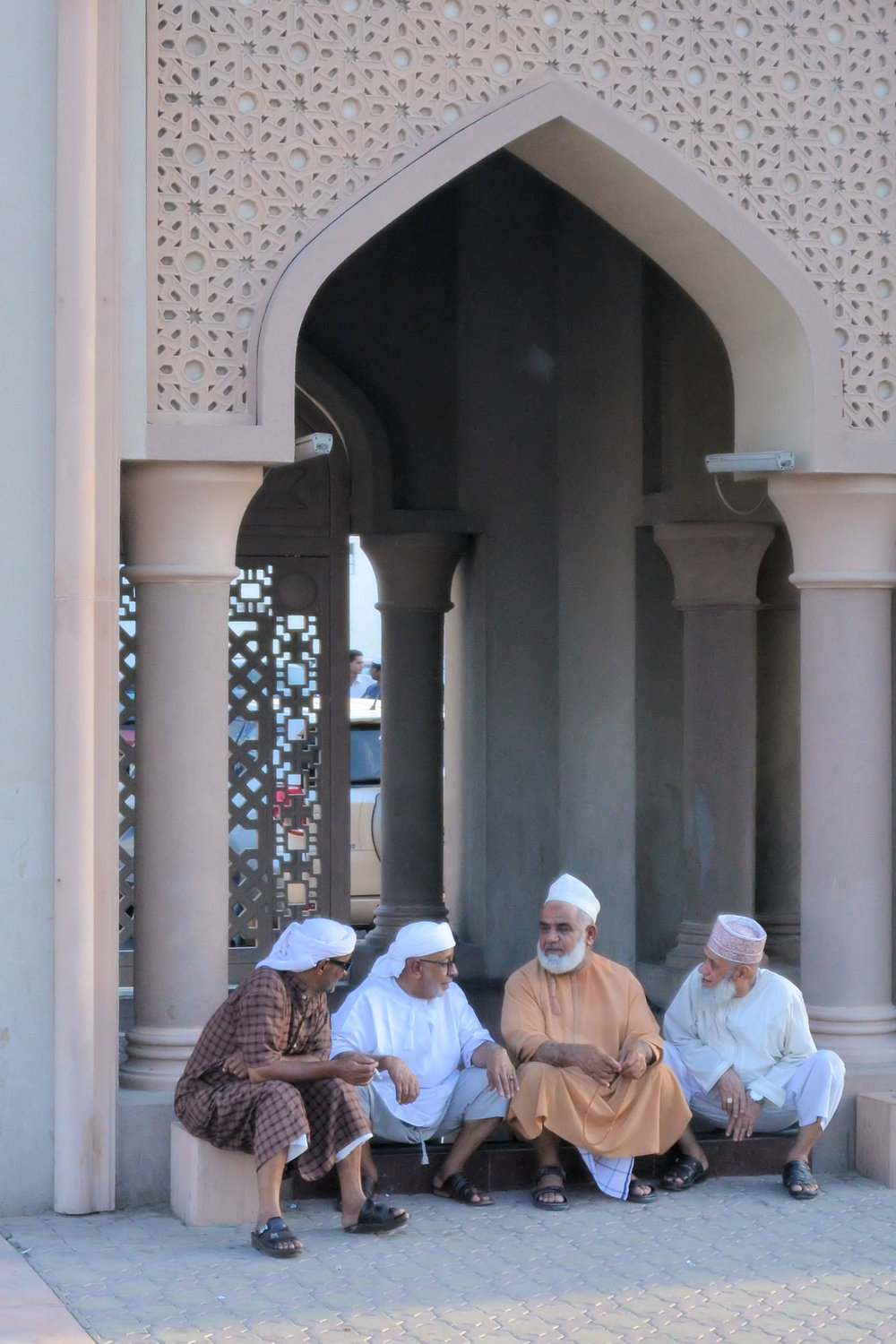 Omani men discuss important matters on the steps of a mosque in Muscat.