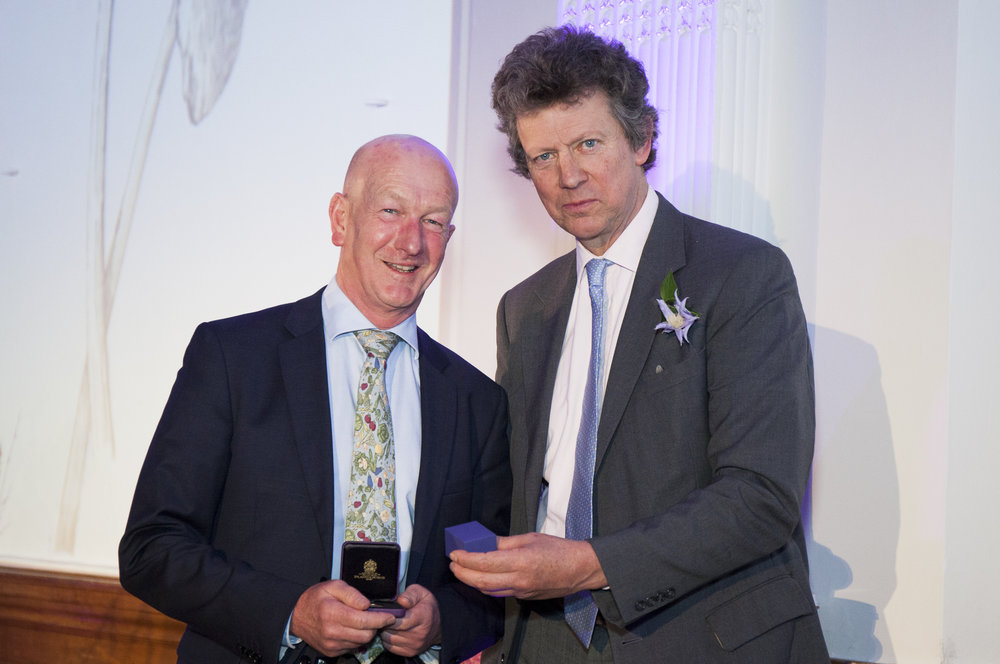 Andy McIndoe is presented with the Veitch Memorial Medal by Sir Nicholas Bacon. President of the RHS at the awards ceremony in the RHS Linley Hall on 22nd February 2017