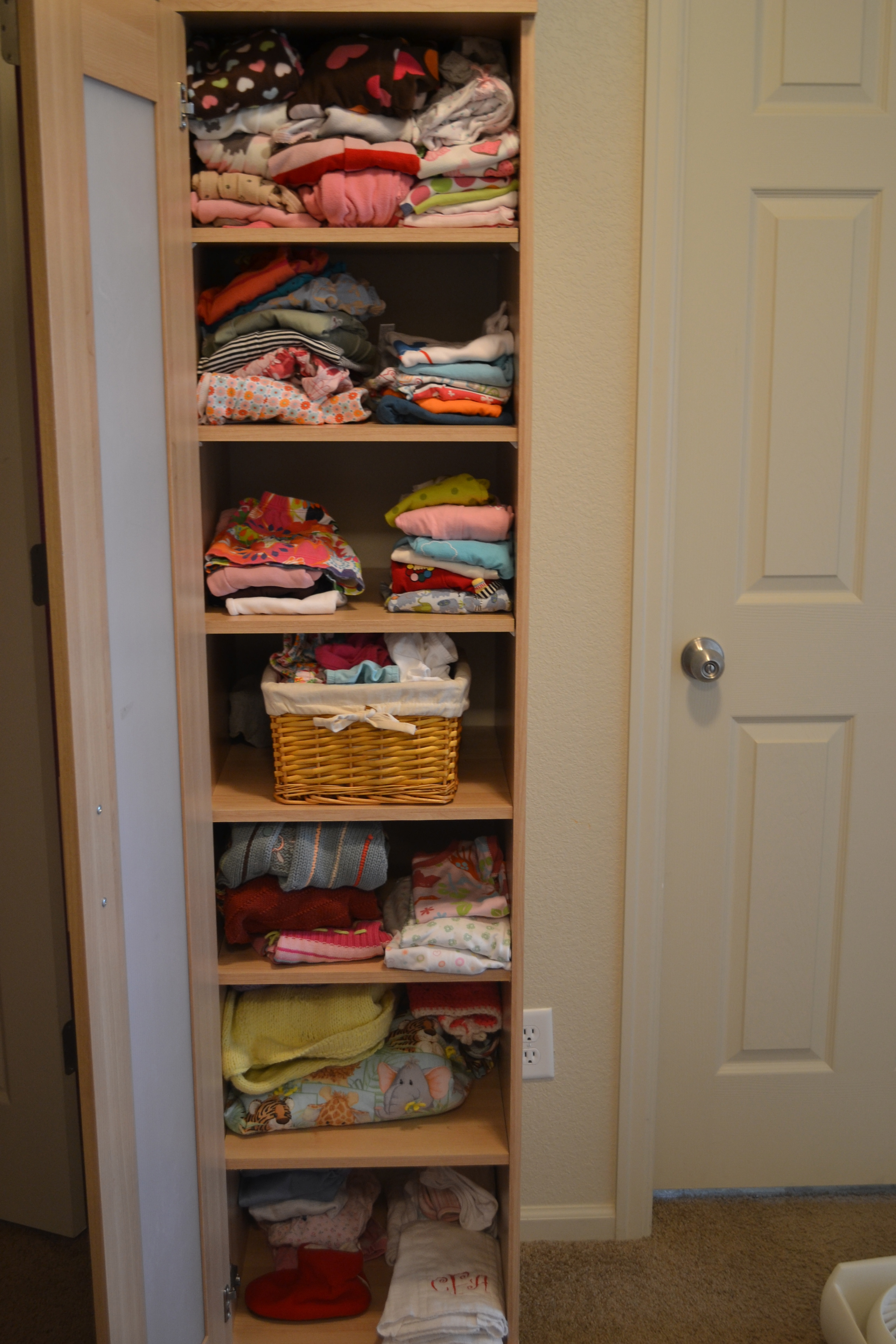 A wardrobe stocked with baby clothes