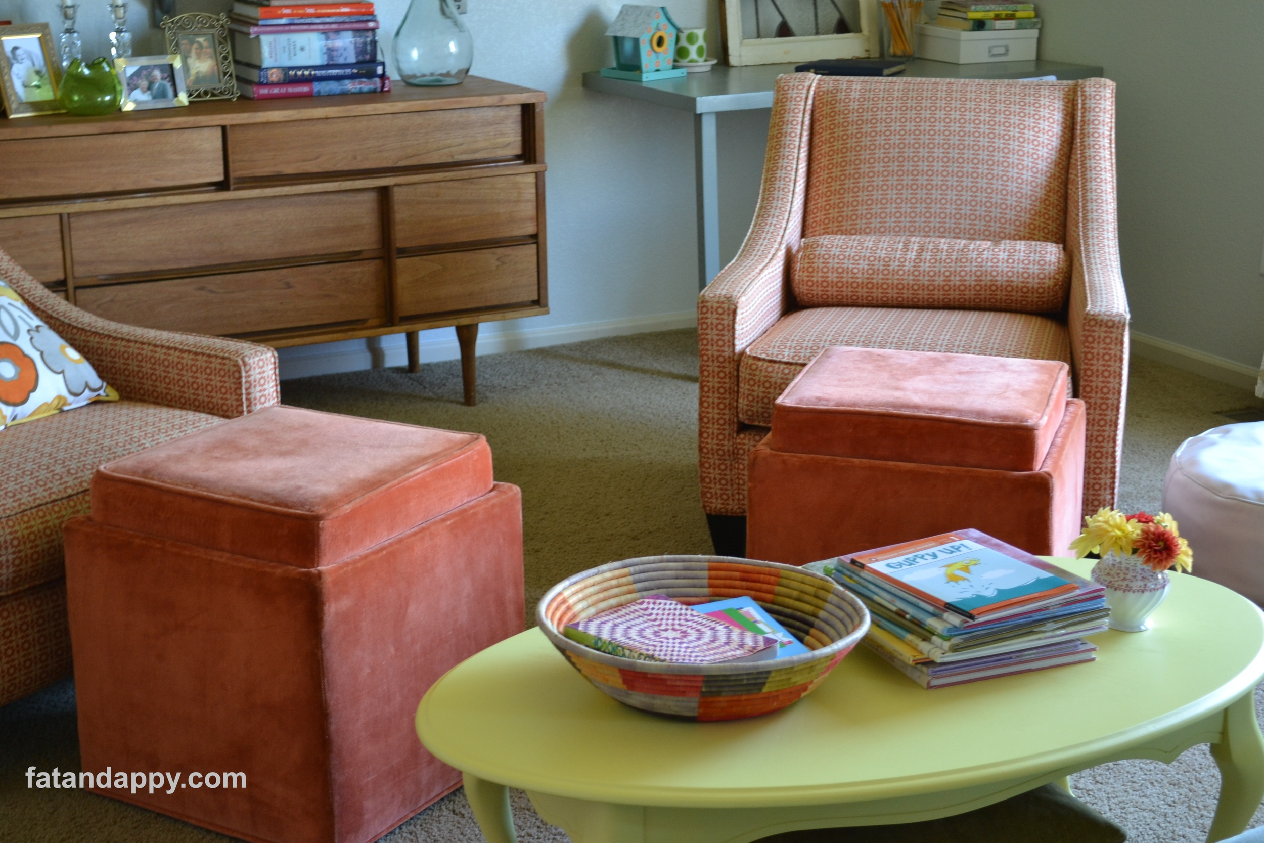 Two orange chairs with a yellow coffee table