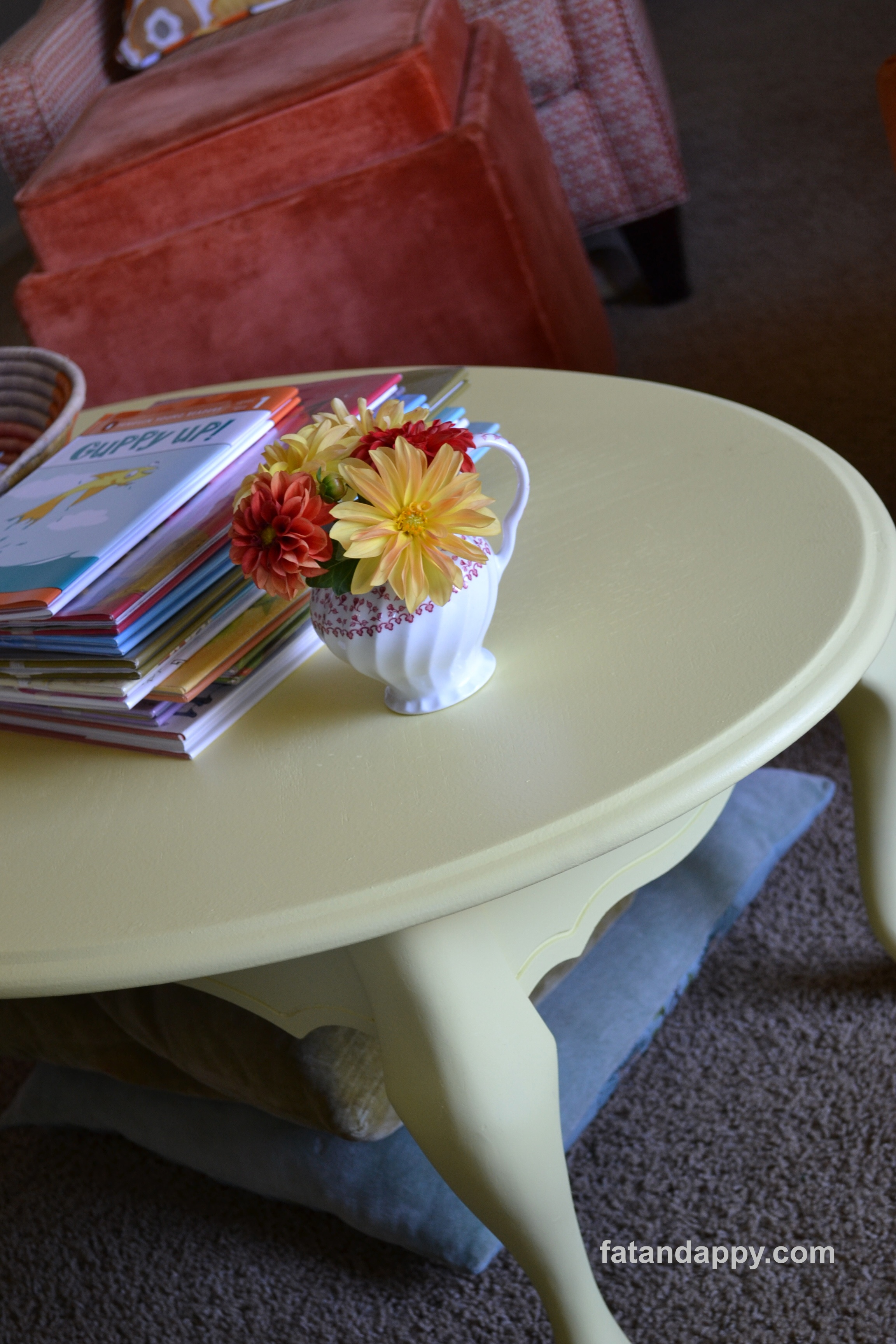 A vase of zinnias on a coffee table painted with Valspar Oatland Daisy