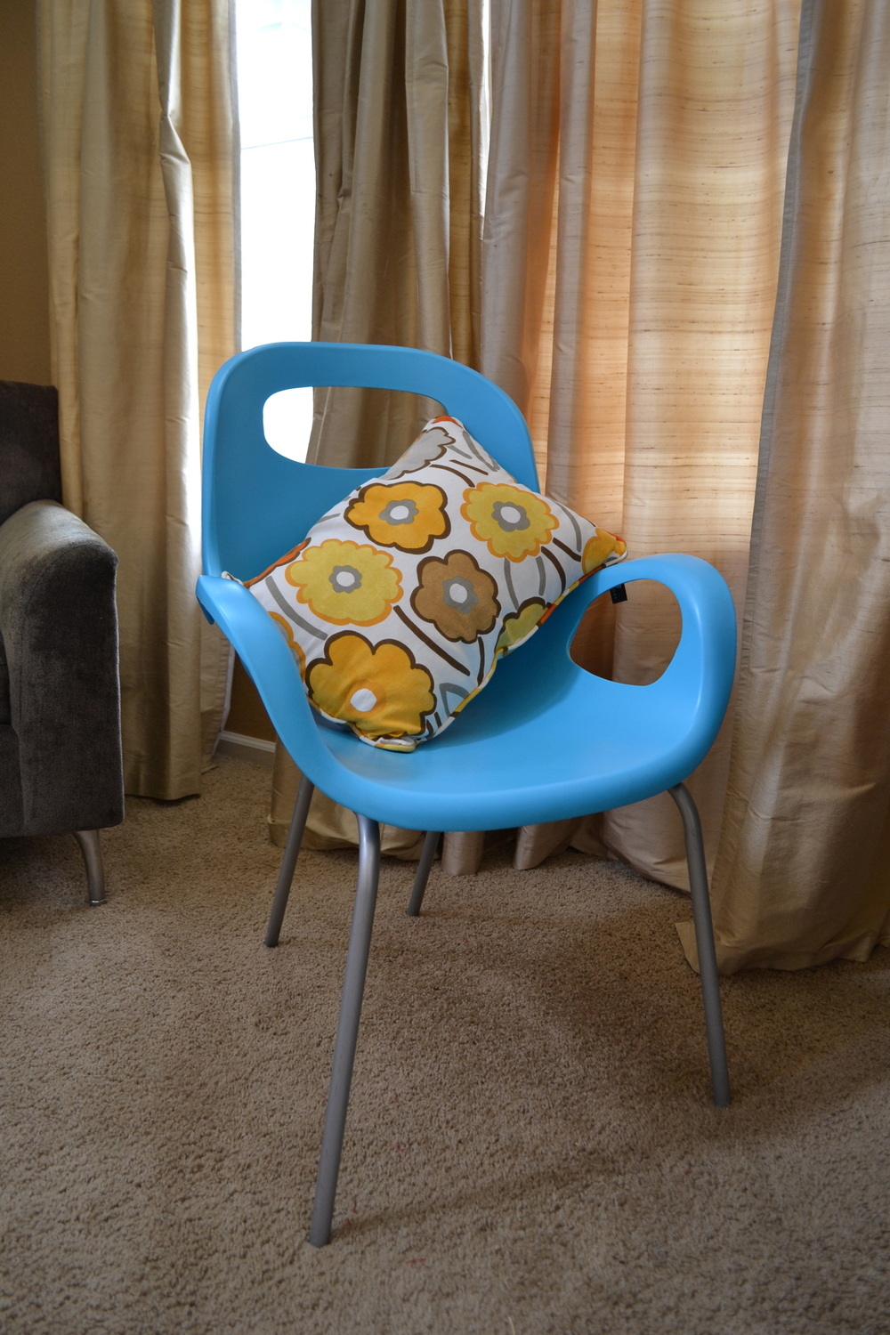 An aqua Umbra chair with flowered pillow