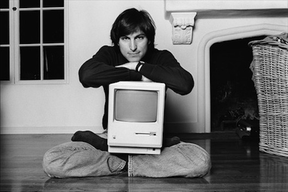 Steve Jobs (1984) in classic lotus pose, cradling the first Mac.