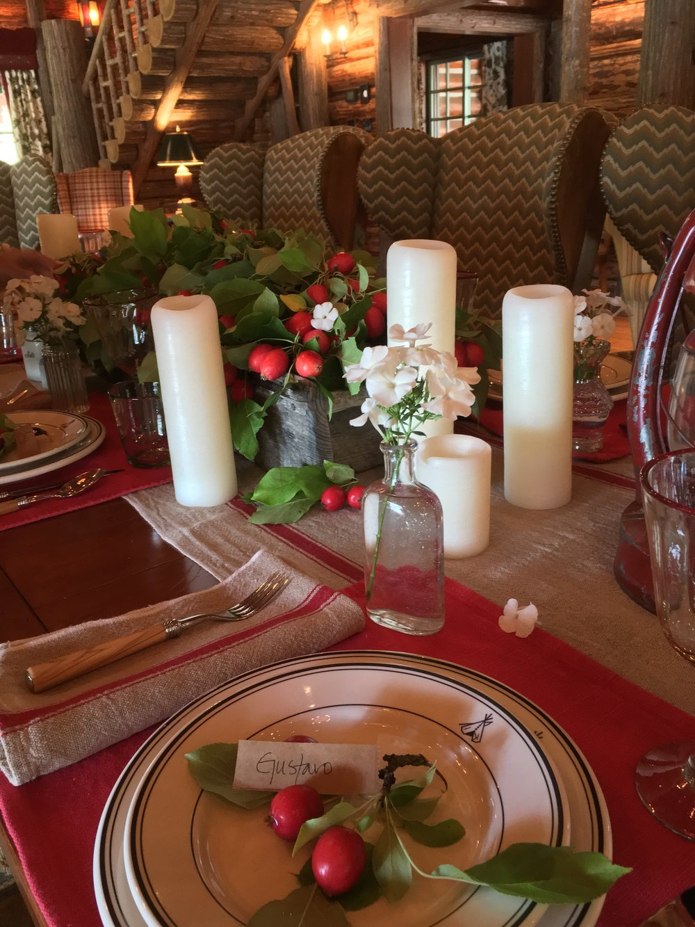 We thought that this table runner and napkin set from Sundance had the perfect rustic charm.  Antique medicine bottles, were used to provide individual floral arrangements at each place setting.  Crab apples served as the  place name display on the center of the Pendleton dinner plates.