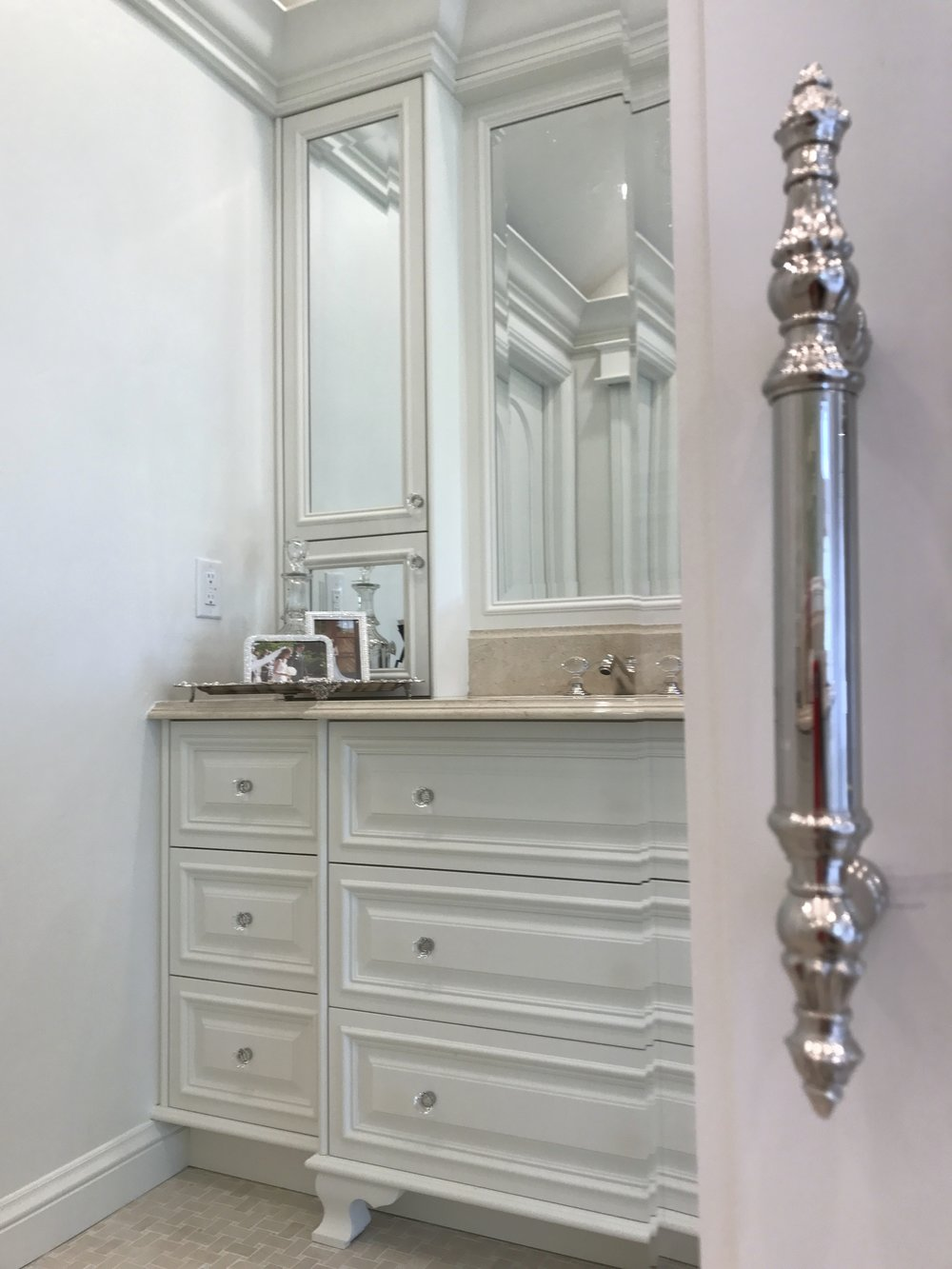 Mirrored sliding doors on the closet have detailed European pulls.  The hardware and crystal handled faucets and controls are the jewelry of the room.