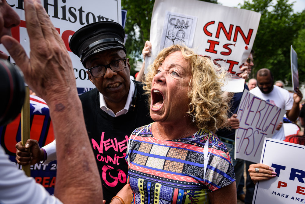 """A woman disrupts the pro-Trump rally in a brief moment of tension, screaming """"Trump has no clothes on"""" at the top of her lungs. She was escorted out by a tour guide (left) without incident."""