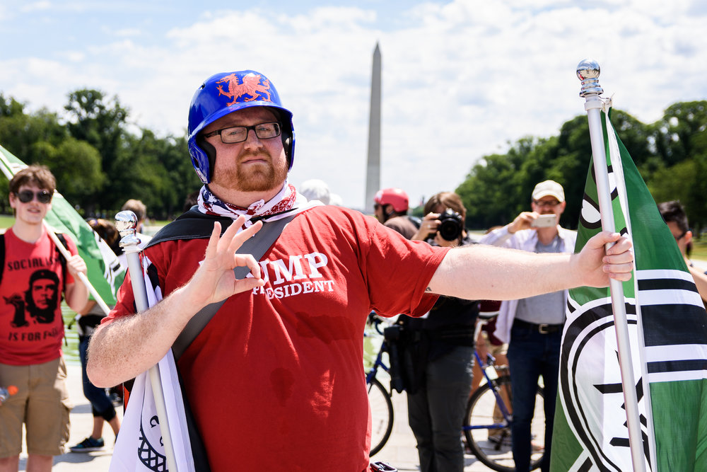 A rally-goer flashes a benign hand sign which online message boards have used to mislead the left by claiming it represents white supremacy.