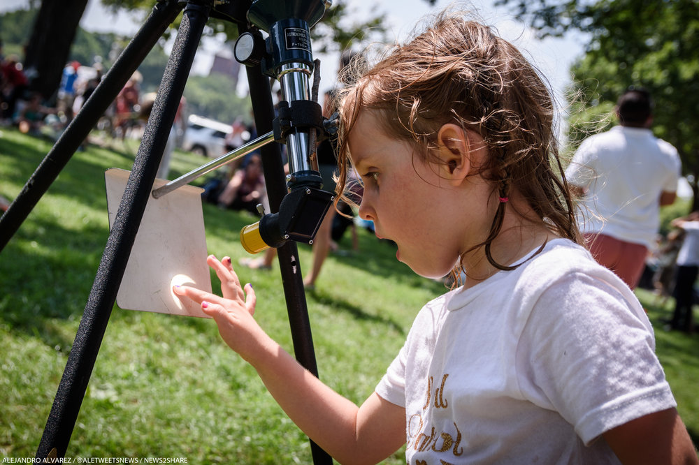 A young girl touches the Sun - or, at least, a projection of it, set up by her father on the National Mall during Monday's solar eclipse.