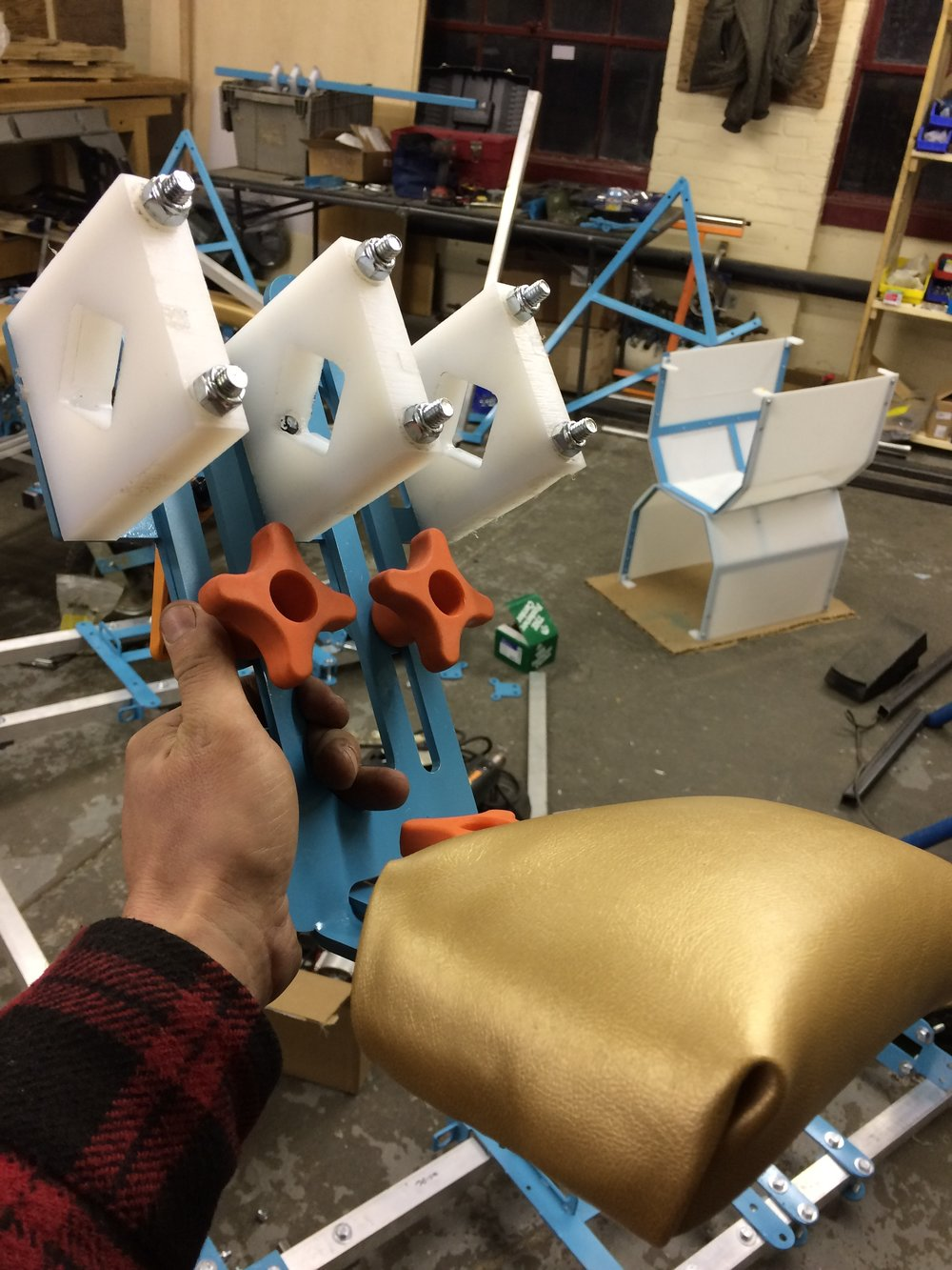 Headrest assembly in the shop. Orange knobs are for adjustments - there's lots of flexibility built in to the body pads