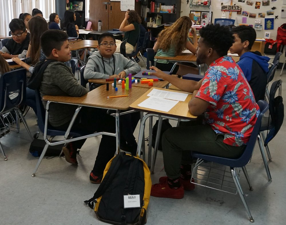 Zavier (BEAM '11), right, supports students in a BEAM 6 LA classroom.