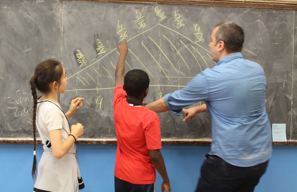 Faculty member Antonio works with students Bakhtigul and Joel on problems in probability at the non-residential program BEAM 6 in New York City.