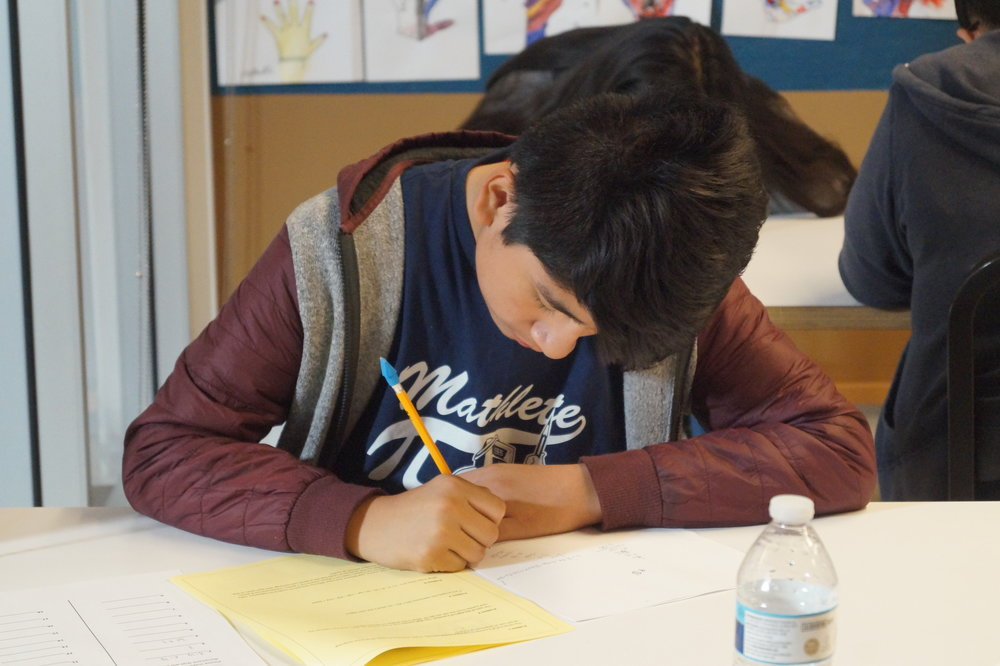 A student from Equitas Academy #2 dons his Mathletes shirt while working on the individual round questions.