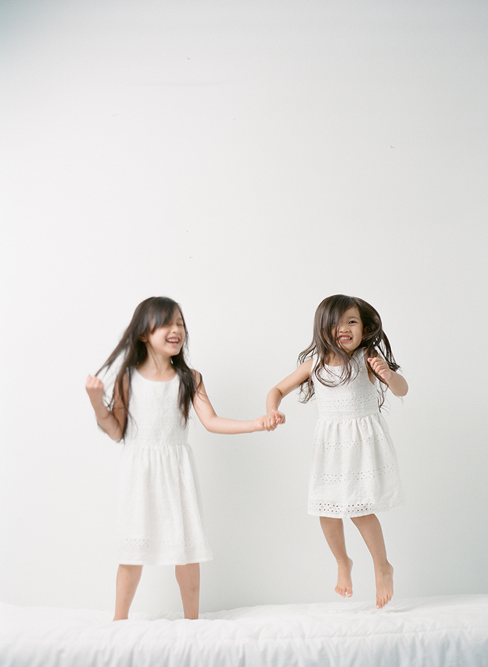 Family photography Seattle, by Sandra Coan. Studio photograph. Sisters jumping on a bed.
