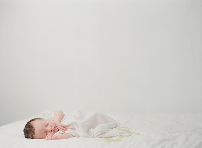 Newborn photography Seattle, by Sandra Coan. Studio photograph.  Newborn sleeping on bed wearing a vintage dress.