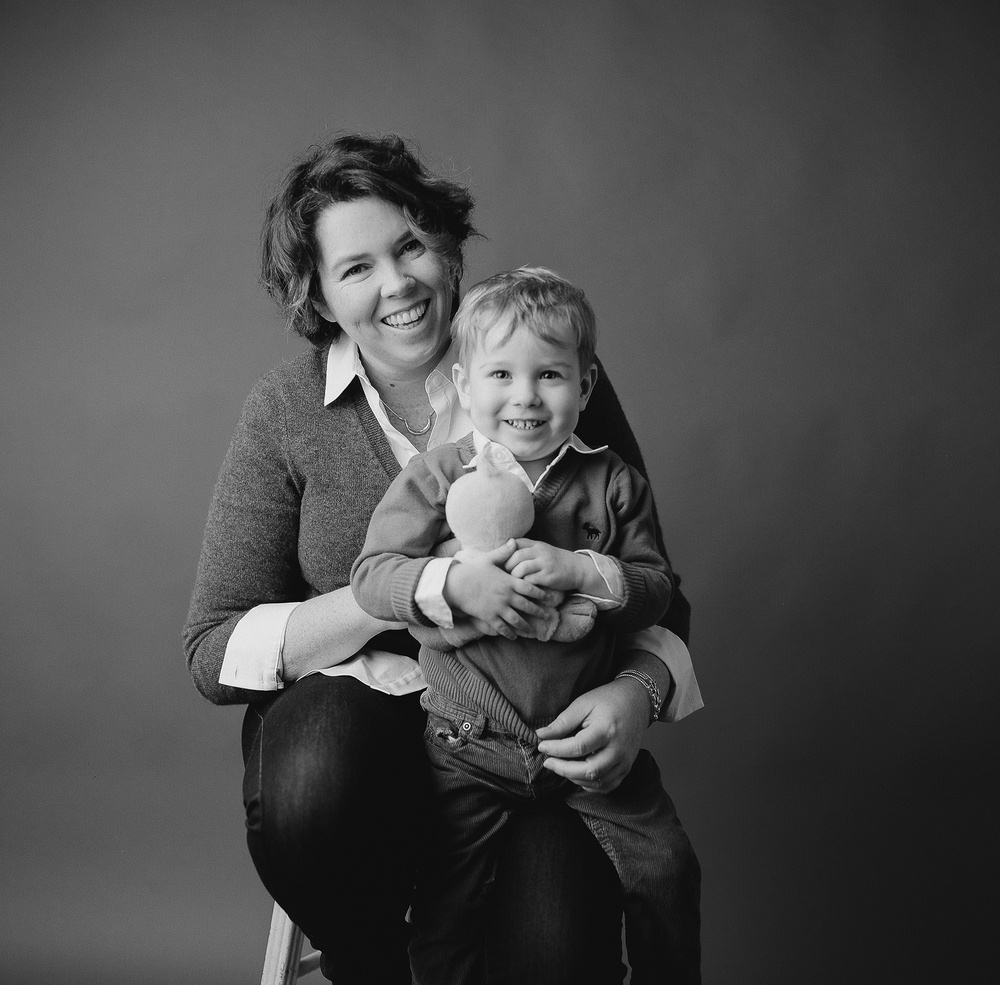 Family photography Seattle, by Sandra Coan. Studio photograph. Black and white photo of little boy sitting on his moms lap.