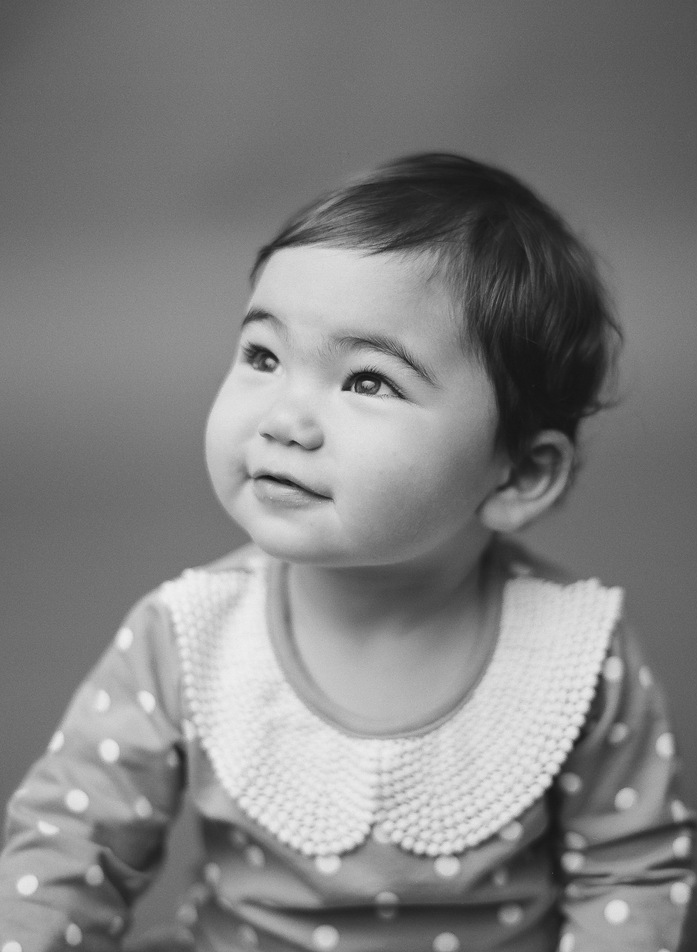 Newborn photography Seattle, by Sandra Coan. Studio photograph. Black and white photo of toddle girl look up at her mom.