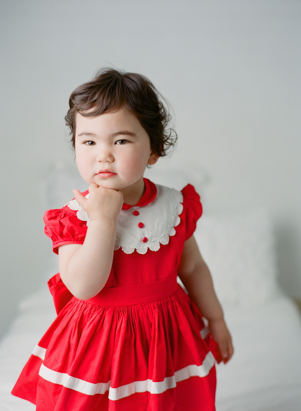 Family photography Seattle, by Sandra Coan. Studio photograph.  Little girl wearing a red dress