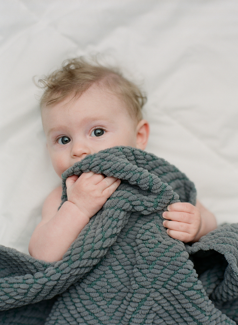Newborn photography Seattle, by Sandra Coan. Studio photograph. Baby peaking up from under a blanket.