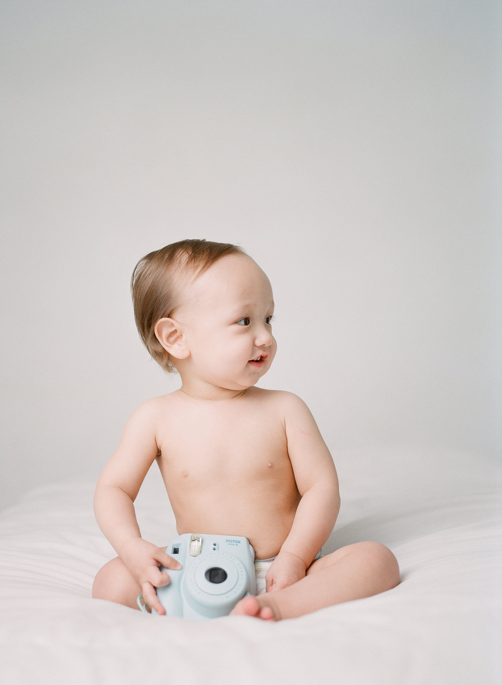 what to bring to a photography studio | bringing props and toys to your studio session | baby's first birthday with toy blue polaroid camera | film photographer sandra coan