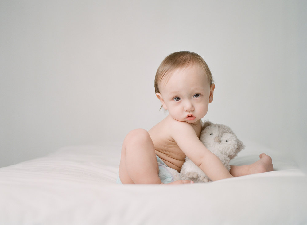 what to bring to a photography studio | bringing props and toys to your studio session | baby's first birthday snuggling plush owl toy on bed | film photographer sandra coan