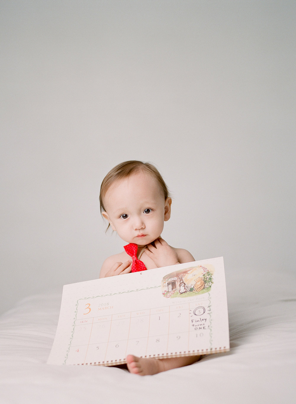 what to bring to a photography studio | bringing props and toys to your studio session | baby's first birthday wearing red bowtie and holding calendar | film photographer sandra coan