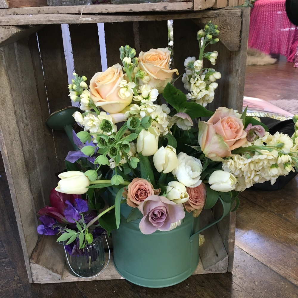 A watering can filled with flowers in an upturned crate make for a relaxed, rustic and natural wedding reception style