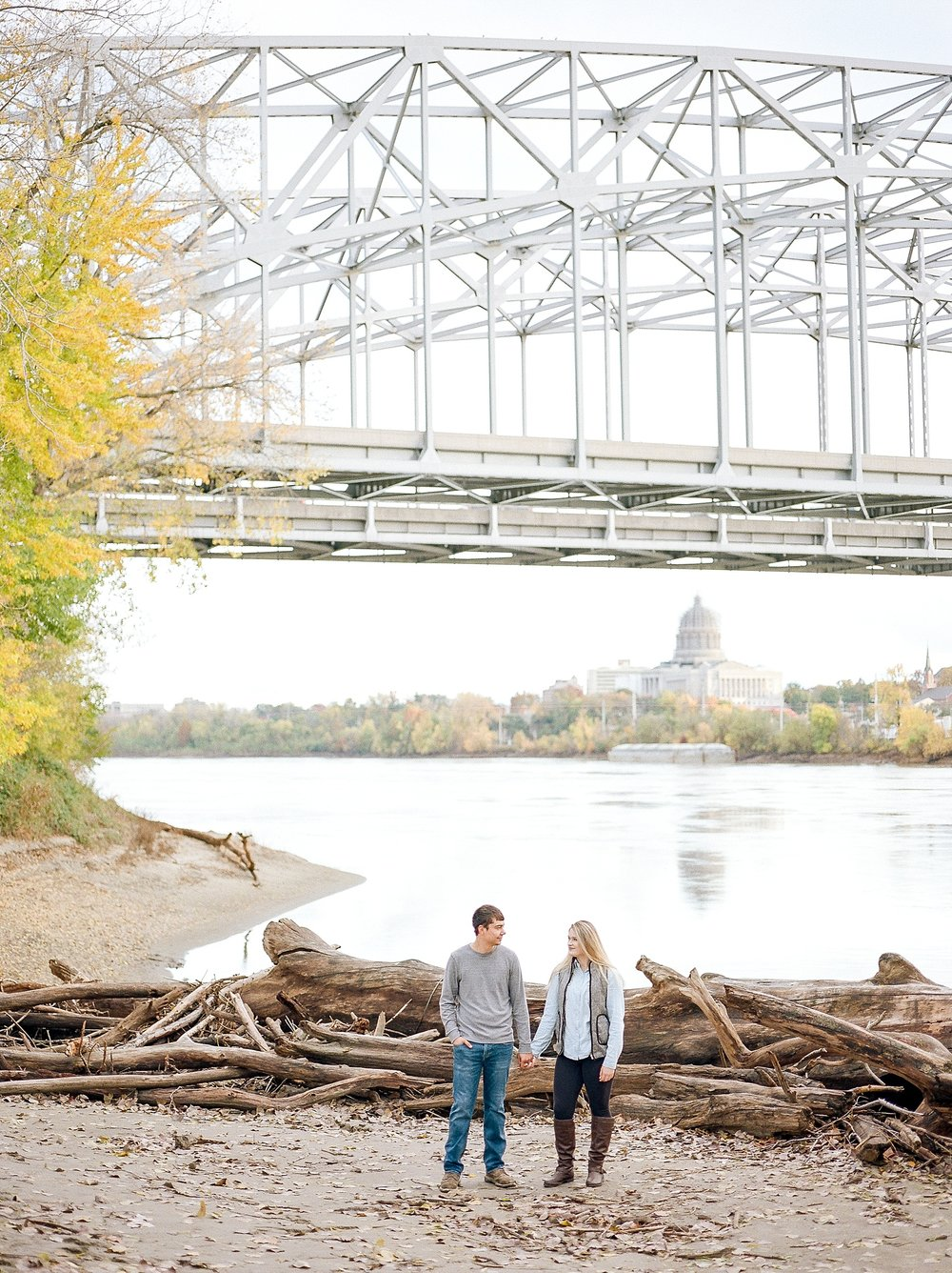 Couple Holding Hands Among Driftwood Shore With Missouri Capitol In Background