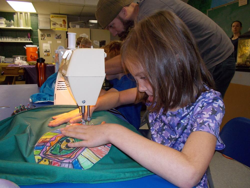 Ruby Lane sews the emblem for her superhero Cat Rocker onto her cape.JPG