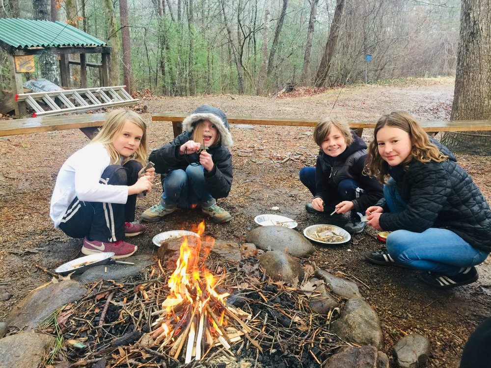 Students working to make fire during their Adventure enrichment.
