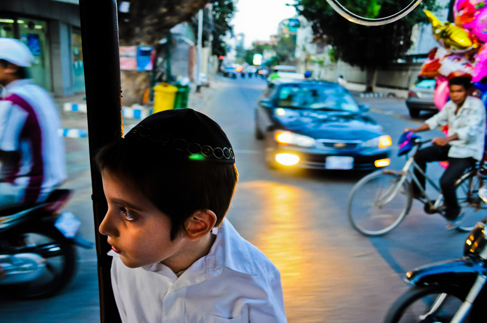 Zalman Butman rides in a tuk tuk on one of Phnom Penh's busiest streets, on his way to pick up his mother at the airport.