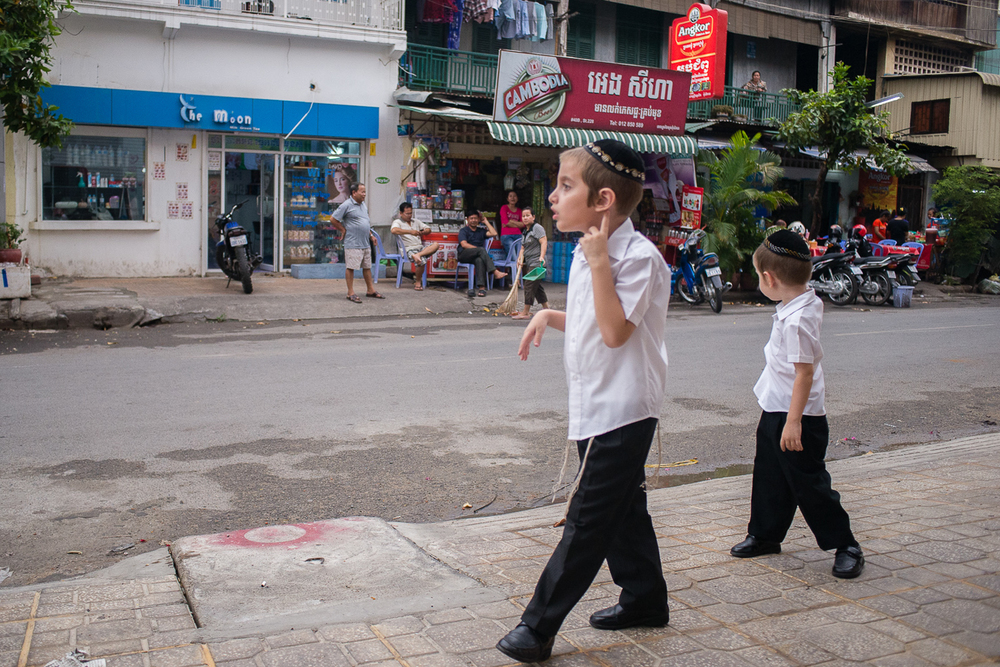 Zalman and his younger brother Shmulik outside their home in Phnom Penh, on their way to walk to Shul (the Jewish Center and Synagogue) down the street. Because the Butmans' observe the Sabbath and do not use transport for 24 hours, their home needs to be close to the center.