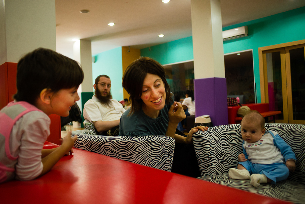 The Rabbi is often at the Jewish Center or attending other meetings around town. It is a rare occurance when the family gets to spend time all together, and they are grateful for it. Pictured here is Mushka, the Rabbi, Mashie, and their youngest son, Moshe.