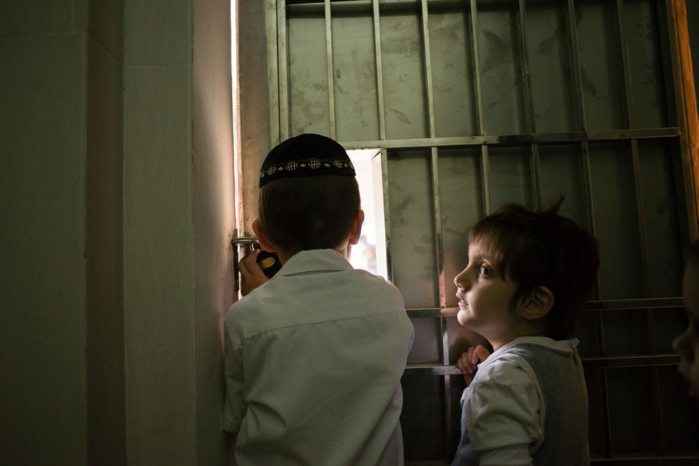 Zalman and Mushka look out onto the street as they wait for Mashie to go to Shul.