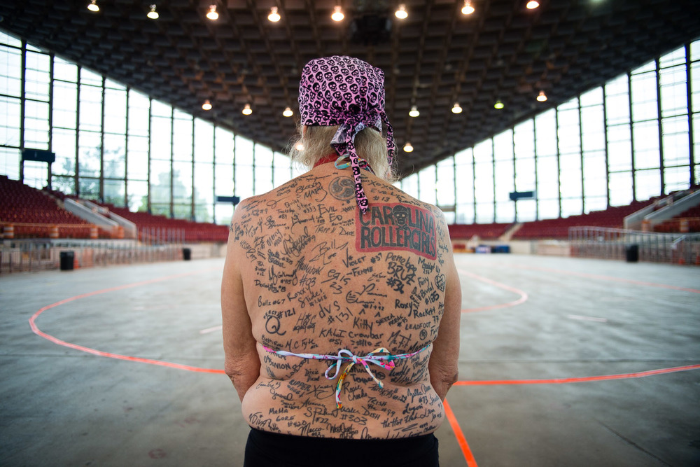 """Double X Factor"" used to play roller derby, and now volunteers at most games running the penalty box. On her back are tatooed signatures from players she respects and admires. ""It is a HUGE honor to be on her back"", says one CRG player."