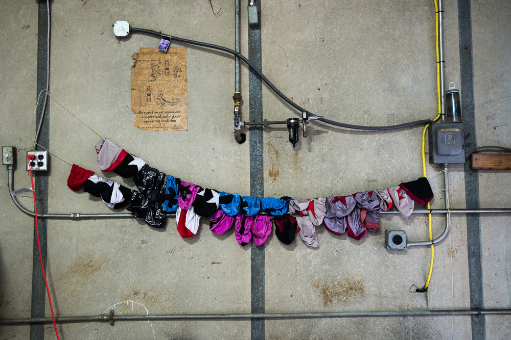 "Positions on the roller derby court are made known by ""panties"", or helmet covers. These hang in CRG's practice space."