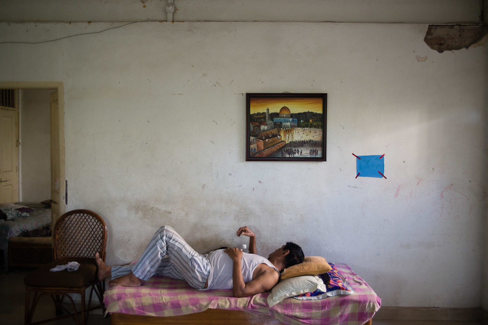 Benjamin Reuben Galsurkar takes a nap under a painting of Jerusalem in the hostel the Galsurkar family owns. The hostel was once a place to house refugees fleeing the Nazis during World War II, and then became a hostel to house Jewish students coming from outside Mumbai to study the religion.