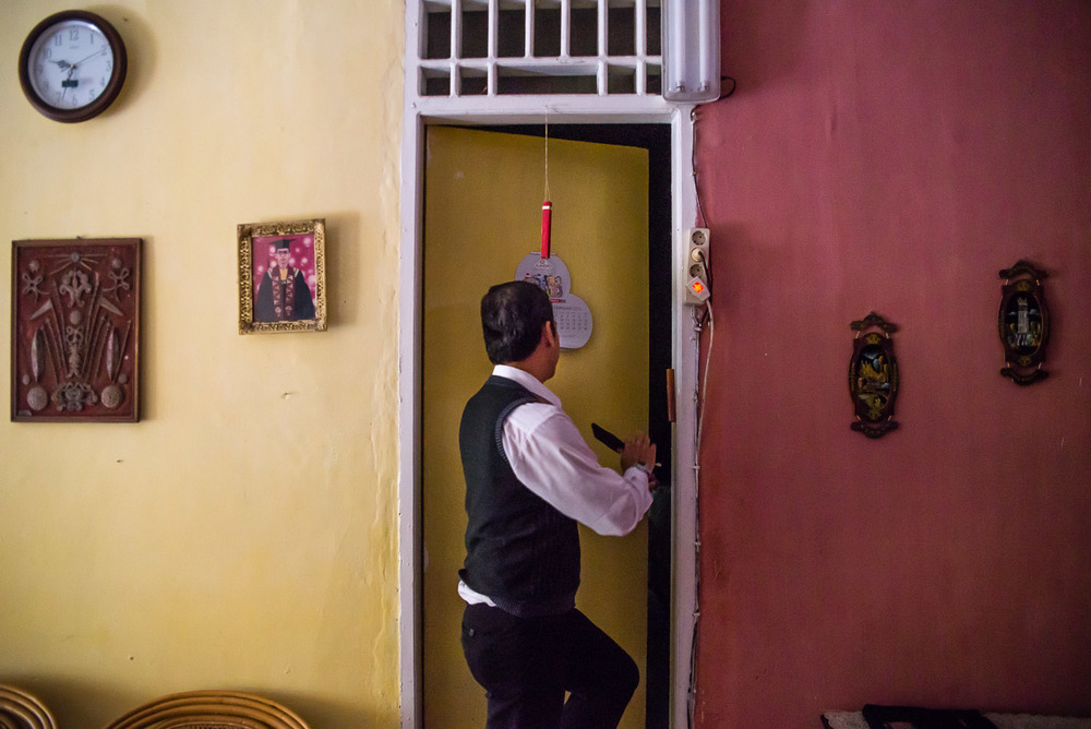 """Benjamin Meijer Verbrugge (Benny), the leader of the United Indonesian Jewish Community, leads the way into his home synagogue in Lampung, Sumatra. """"This door marks where Kosher begins. My house, it can't always be Kosher. But inside the synagogue it is""""."""