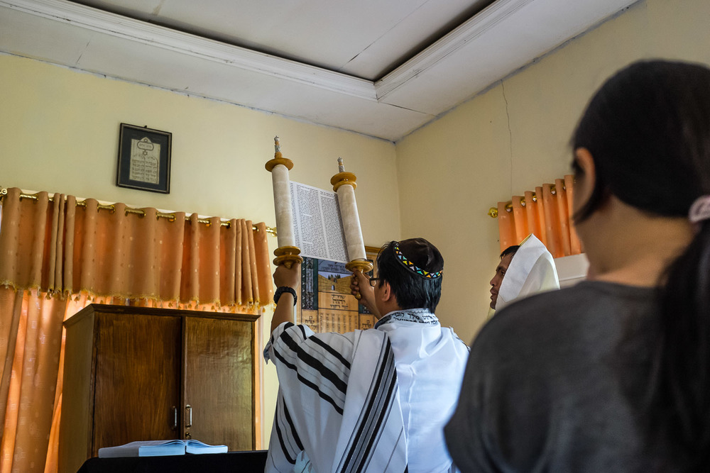 Vicktor (Noakh) holds the Torah during Saturday morning services in Manado.