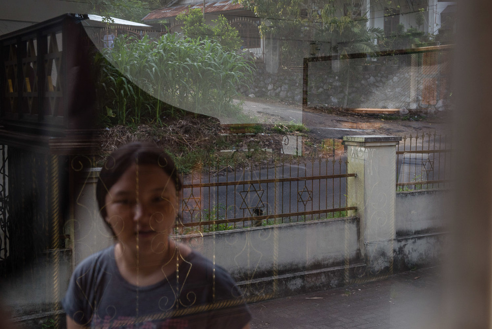 Ezra's daughter's face is reflected in the window of the locked synagogue in Manado. While Ezra's family came to pray at Vicky's home synagogue, Ezra is still somewhat affiliated with another group in Manado (with supposed links to the church) and so he prayed with them elsewhere. The synagogue was paid for by a Dutch Jewish woman who felt strongly about the community in Indonesia, but it is far away from Manado and not often used.
