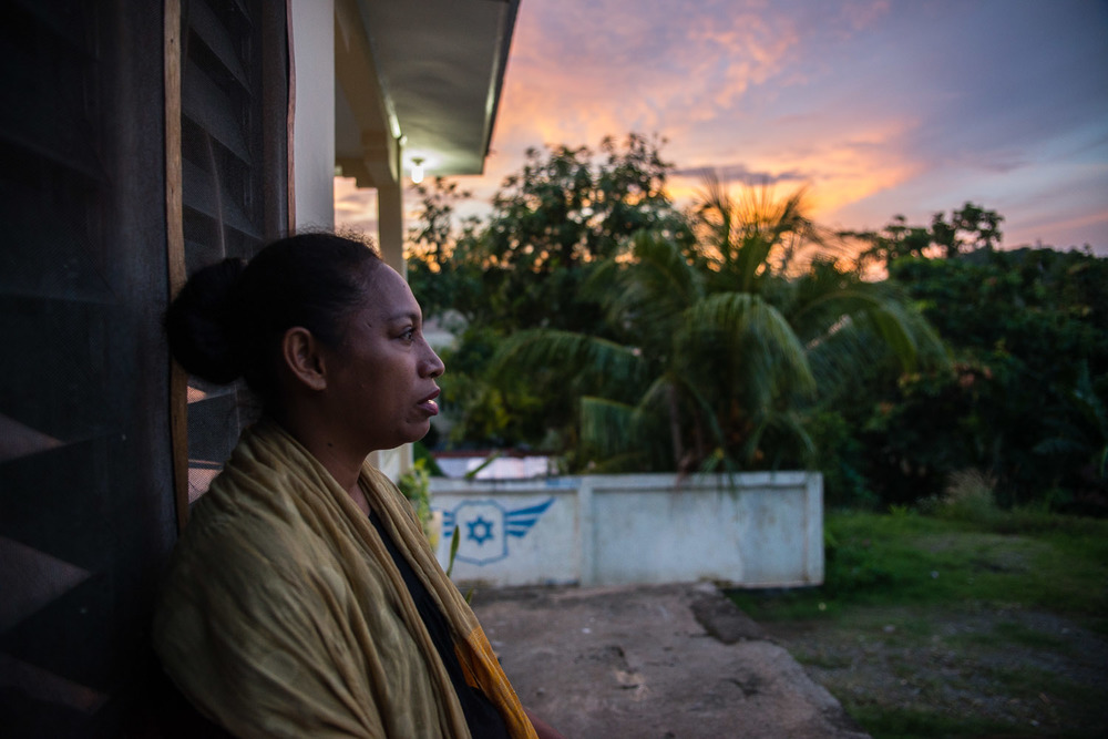 "Diane Hokouoku sits outside her home which also serves as the main synagogue for the Jewish community in Jayapura, West Papua, Indonesia. She visited Israel once and remembers ""I tried to get up every day to see the sunshine. I wanted to know what it looked like in Israel. It was beautiful, so many colors. We live in the Far East, here, but in Israel is in the middle. I would look east and see, far away, there is Jayapura."""