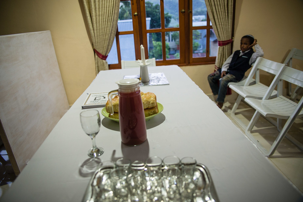 A young member waits for Friday night Shabbat services to begin. The grape juice set on the table is homemade by Harun or Diane every week, and the children get especially excited for a sweet treat.