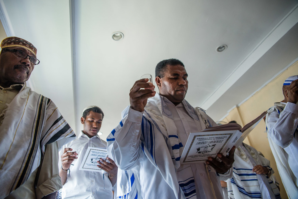 Men pray in the home synagogue in Jayapura, Papua, Indonesia, on Saturday morning Shabbat services. They read from books that have Hebrew, a transliteration of the Hebrew, and a Bahasa Indonesia translation.