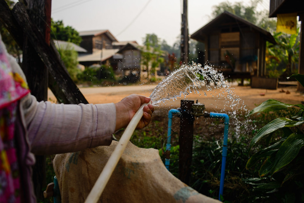 Suwat Jutnai's wife waters the plants outside their home in Fack Huay (Gok Sathon). The local TAO, or district government, now pipes in clean water to the affected villages at the insistence of the Ministry of Health.